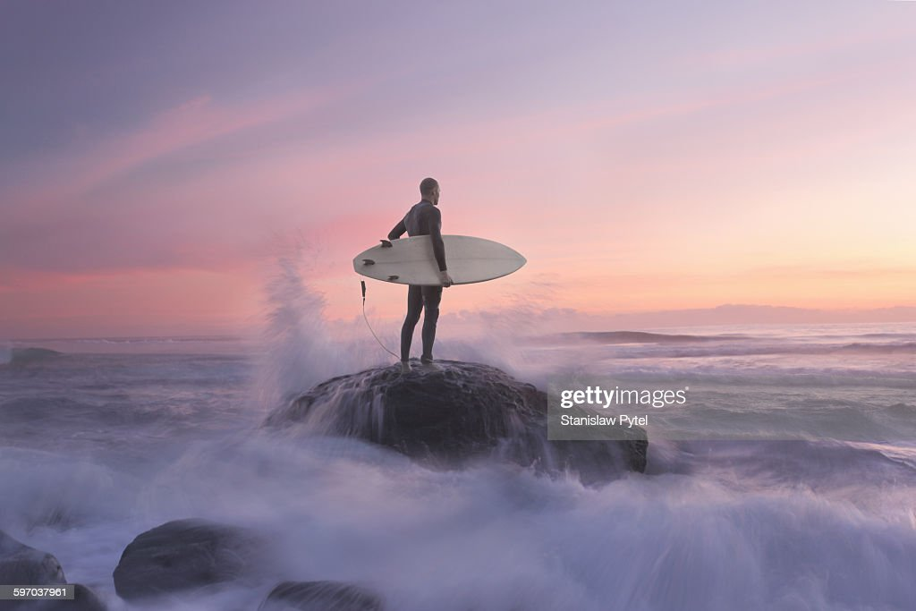 Surfer on rock against sunset, water around : Stock Photo