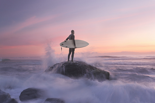 Surfer on rock against sunset, water around - gettyimageskorea