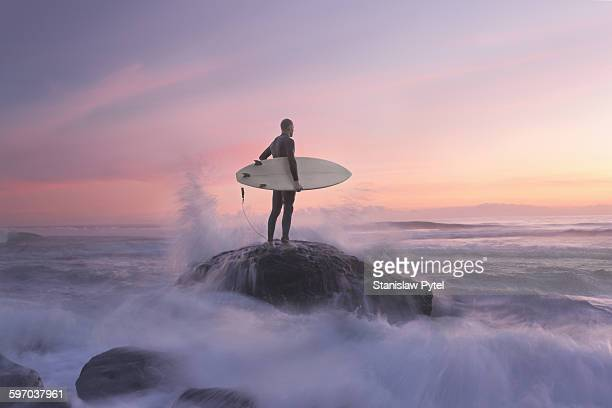 surfer on rock against sunset, water around - coraggio foto e immagini stock