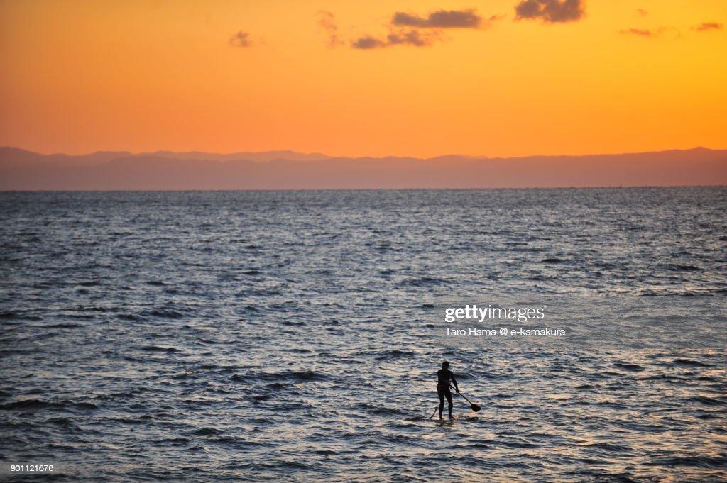 A surfer on sunset beach in Kamakura city in Kanagawa prefecture in Japan : ストックフォト