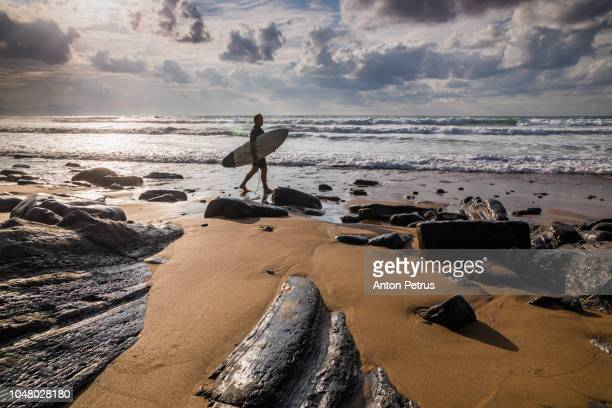 Surfer on the background of a dramatic sky at sunset. Spain, Atlantic Ocean