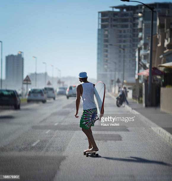 Surfer on the way to the beach on longboard
