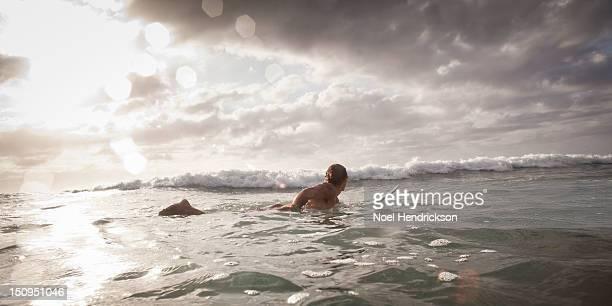 a surfer paddles out to catch waves - esperar imagens e fotografias de stock