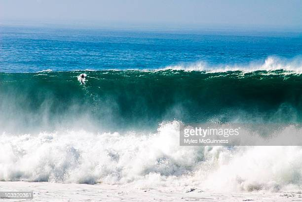 A surfer paddles over a giant wave at Blacks Beach in San Diego, California.