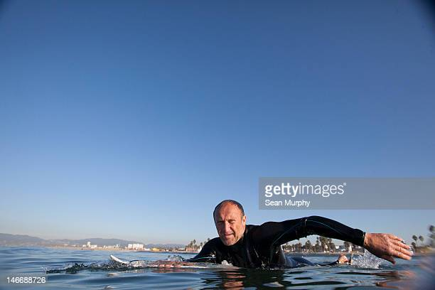 Surfer Paddling on Calm Ocean Water