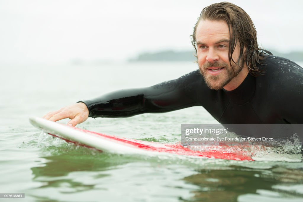 Surfer paddling on surfboard in sea : Stock Photo