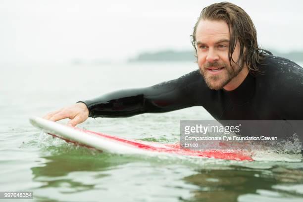 Surfer paddling on surfboard in sea