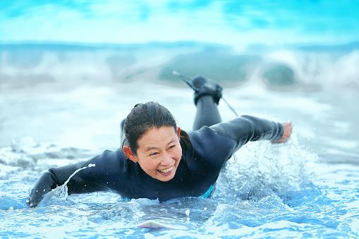 Surfer paddling with surfboard on Japanese beach in splash. - gettyimageskorea