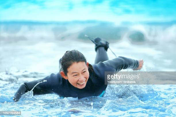 surfer paddling with surfboard on japanese beach in splash. - fitness or vitality or sport and women stock photos and pictures