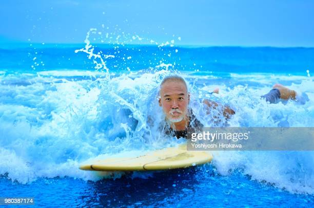 Surfer paddling with surfboard on Japanese beach in splash.