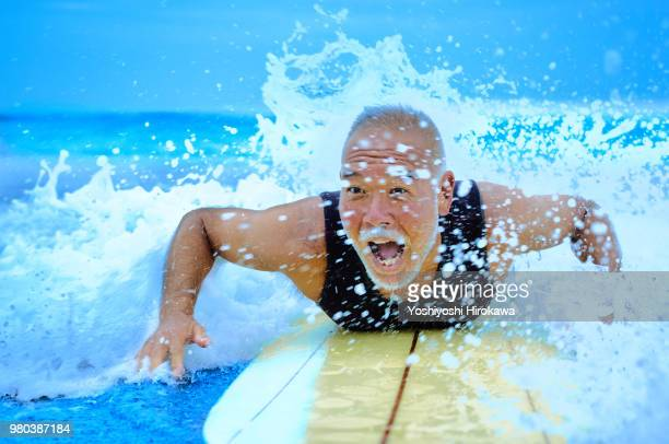 surfer paddling with surfboard on japanese beach in splash. - activiteit bewegen stockfoto's en -beelden