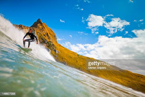 surfer passing by castle rock at castlepoint surf break. - wellington new zealand stock pictures, royalty-free photos & images