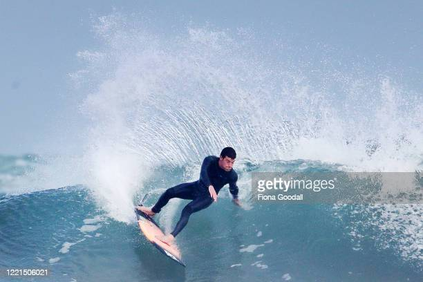 Surfer Paul Moretti 24 of Muriwai catches a wave at Maori Bay on April 28 2020 in Auckland New Zealand Today is the first day Paul has been able to...