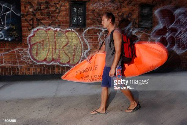 Surfer Paul Treacy carries his surfboard to the New York City Subway August 2 2001 as he starts his hourlong trek from his Manhattan apartment to...