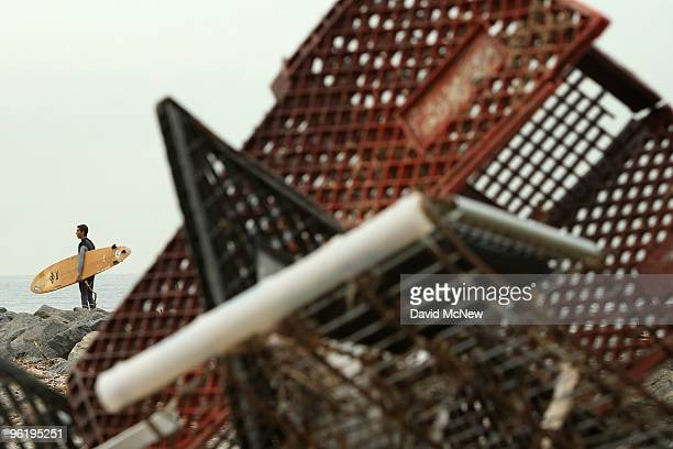 Surfer pauses to evaluate the break before going in near a pile of shopping carts gathered by city workers cleaning up trash and debris from the...