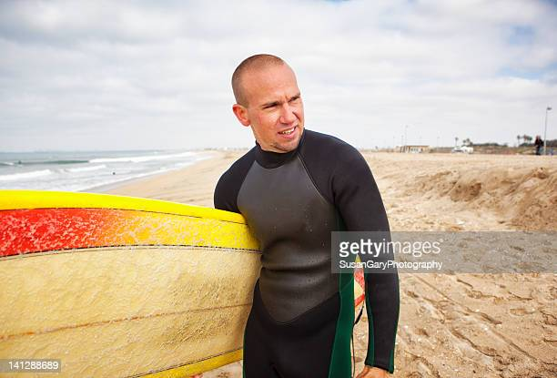 Surfer Poses With Surfboard