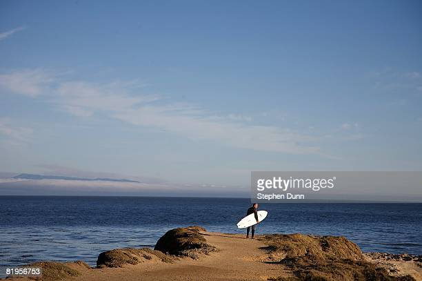 A surfer prepares to jump off the cliffs into the Pacific Ocean at Steamer Lane a well known surfing spot on July 3 2008 in Santa Cruz California