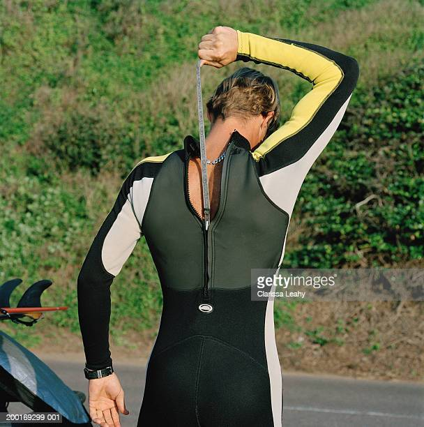 Surfer pulling up zip on wetsuit, mid section, rear view