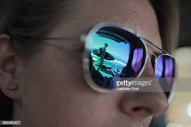 Surfer reflecting in glasses of woman