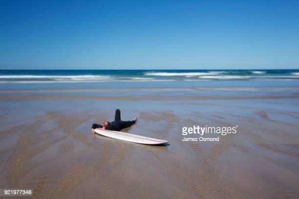 Surfer relaxing on his surfboard at the shoreline