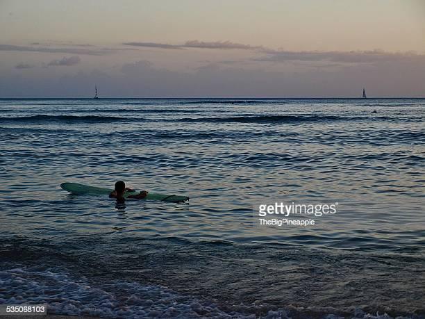 Surfer rests beside surfboard in water