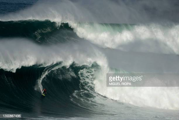 TOPSHOT A surfer rides a big wave at the Praia do Norte in Nazare on February 15 2020