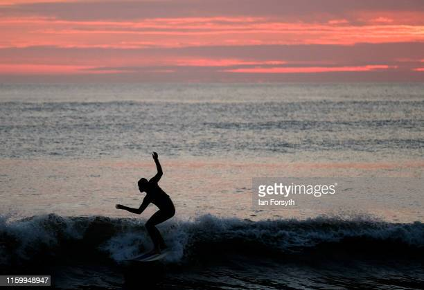 A surfer rides a wave as he surfs at first light on July 04 2019 in SaltburnByTheSea England