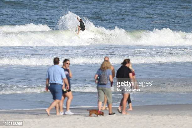 A surfer rides a wave as people gather along the beaches in its first open hour on April 17 2020 in Jacksonville Beach Fl Jacksonville Mayor Lenny...