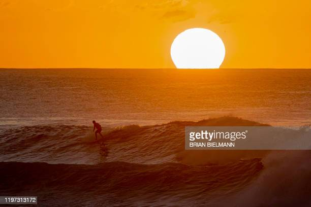 TOPSHOT A surfer rides a wave as the sun sets on the horizon ahead of the Volcom Pipe Pro at Backdoor Pipeline on the north shore of Oahu in Hawaii...