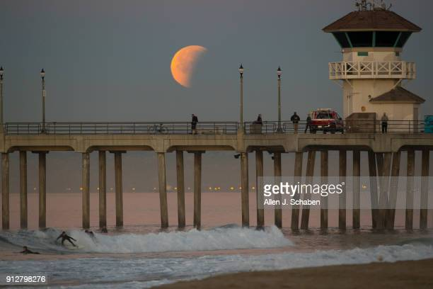 A surfer rides a wave as the super blue blood moon eclipse sets over the Huntington Beach pier January 31 2018