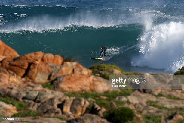 A surfer rides a wave at Cowaramup Bay on June 27 2015 in Gracetown Australia Monster swells were predicted for the south west coast across Friday...