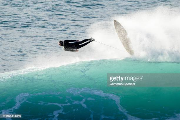 Surfer rides a wave at 'Deadmans' off Shelly Headland on July 16, 2020 in Sydney, Australia. The Bureau of Meteorology has issued a severe weather...