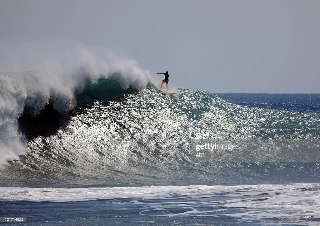 A surfer rides a wave at Le Port beach o : News Photo