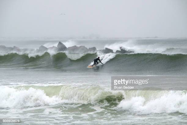 Surfer rides a wave at Rockaway Beach during a snow storm March 21, 2018 in the Queens borough of New York. New York City and much of New England has...