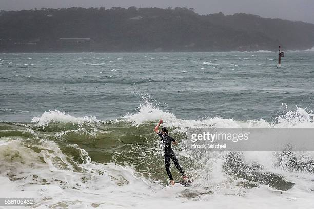 A surfer rides a wave at Shark Beach Vaucluse on June 5 2016 in Sydney Australia Located inside Sydney harbour the rarely surfed waves at Shark beach...