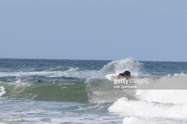 A surfer rides a wave during the beaches first open hour on April 17 2020 in Jacksonville Beach Fl Jacksonville Mayor Lenny Curry opened the beaches...