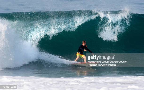 A surfer rides a wave in Newport Beach on Friday August 10 2018 A swell from Hurricane John will bring larger waves to southfacing beaches through...