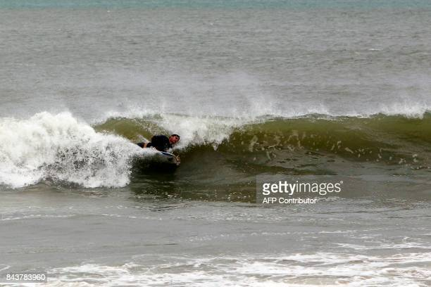 A surfer rides a wave in the waters at La Pared Beach in the aftermath of Hurricane Irma in Luquillo on September 7 2017 One of the most powerful...
