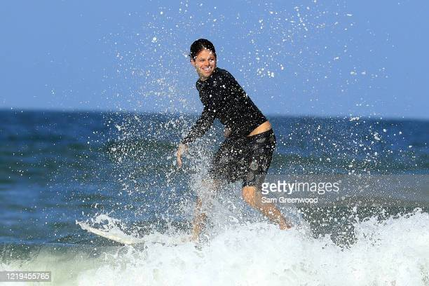 A surfer rides a wave on April 17 2020 in Jacksonville Beach Florida Jacksonville Mayor Lenny Curry announced Thursday that Duval County's beaches...