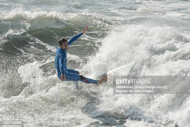 A surfer rides a wave south of the pier in Huntington Beach on Friday Jan 19 2018
