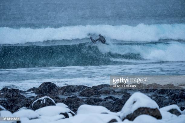 TOPSHOT A surfer rides a wave under snowfall on March 11 in Unstad northern Norway Lofoten islands within the Arctic Circle MORIN