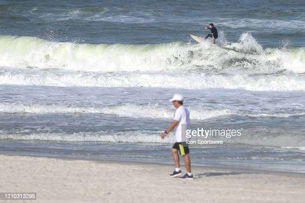 A surfer rides a wave while a man walks during the beaches first open hour on April 17 2020 in Jacksonville Beach Fl Jacksonville Mayor Lenny Curry...