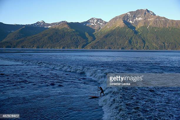 A surfer rides the Bore Tide at Turnagain Arm on July 14 2014 in Anchorage Alaska Alaska's most famous Bore Tide occurs in a spot on the outside of...