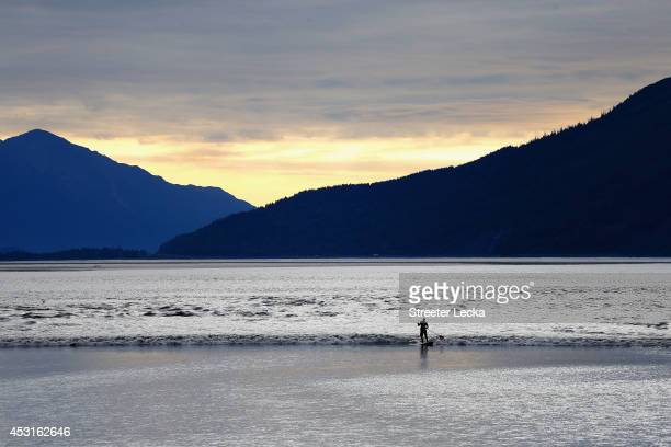 A surfer rides the Bore Tide late in the evening at Turnagain Arm on July 15 2014 in Anchorage Alaska Alaska's most famous Bore Tide occurs in a spot...