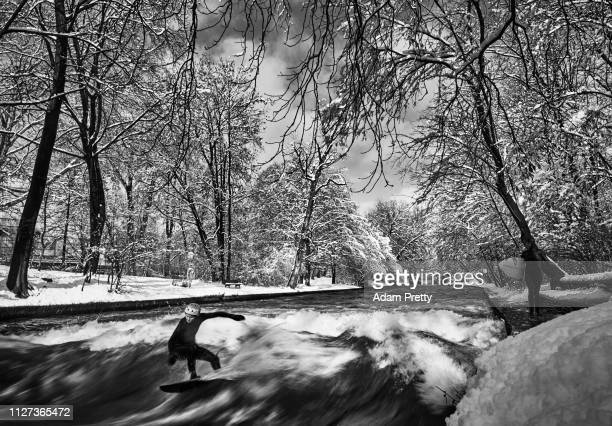 A surfer rides the Eisbach wave in the English Garden on February 4 2019 in Munich Germany The Eisbach wave is a manmade wave in the river that the...