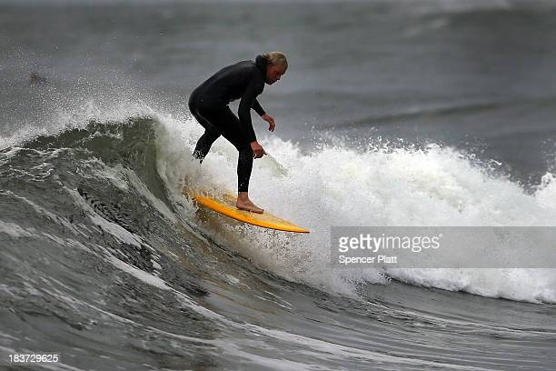 Surfer rides the morning waves at Rockaway beach on October 9, 2013 in the Queens borough of New York City. Nearly one year after Hurricane Sandy...