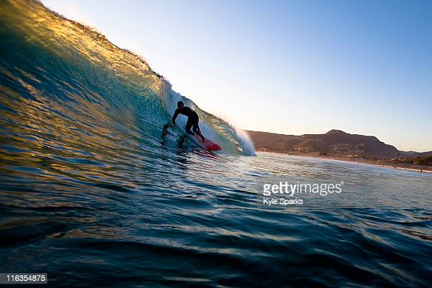 A surfer riding a red surfboard sets up for a barrel while surfing at Zuma Beach in Malibu, California.