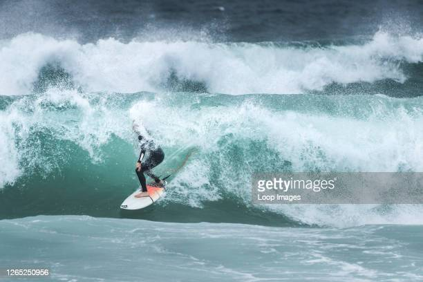 Surfer riding a wave at Fistral Beach in Newquay in Cornwall.