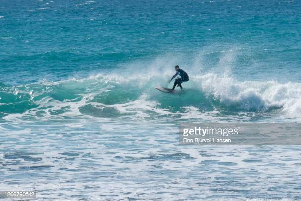surfer riding a wave making a left turn - finn bjurvoll stock pictures, royalty-free photos & images