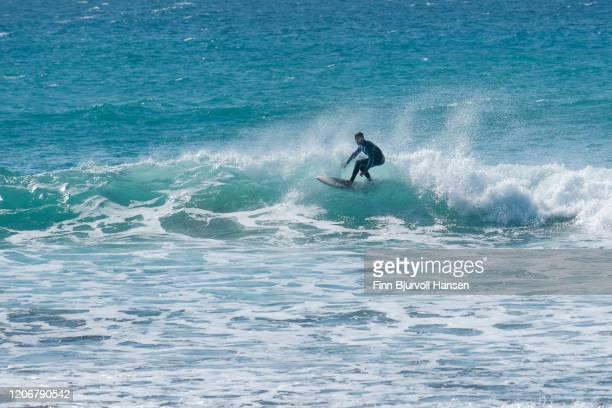 surfer riding a wave making a left turn - finn bjurvoll stockfoto's en -beelden